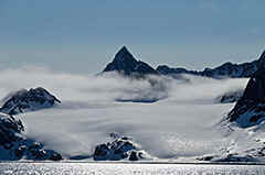 Another 'spits' mountain in the clouds and surrounded by glaciers.